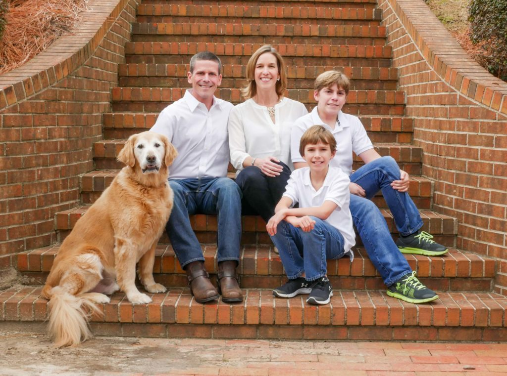Family photo taken outdoors on the steps of their home with the dog Dalton, Ga
